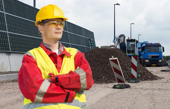 Road construction worker, wearing an overall, safety vest and other safety precautions, overlooking the building site, with a dump truck and digger in the background, behind a pile of gravel and road markings
